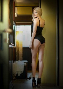 Attractive fair hair model with black corset standing in door frame. Fashion portrait of a sensual woman, rear view, indoors shot. Beautiful blonde on high heels in black posing provocatively.