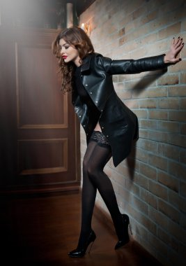 Charming young brunette woman in leather coat over black stockings posing near red bricks wall. Sexy gorgeous young woman on high heels. Full length portrait of sensual woman with long curly hair