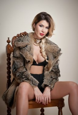 Attractive and sexy blonde woman with black lingerie and fur coat posing provocatively sitting on chair, gray background. Sensual female with fair hair and beautiful legs looking into the camera