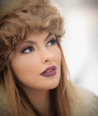 Attractive young Caucasian adult with brown fur cap. Beautiful blonde girl with gorgeous lips and eyes wearing fur hat, outdoor shot. Makeup - sensual long fair hair female art portrait, winter season