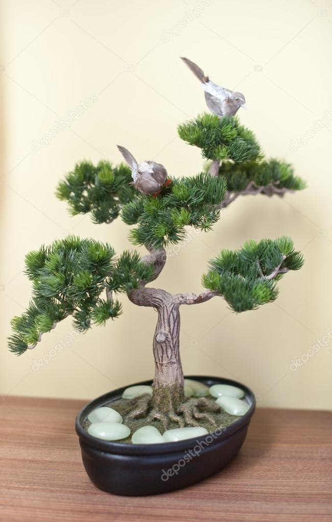 A small bonsai tree in black ceramic pot on wooden table on yellow a small bonsai tree in black ceramic pot on wooden table on yellow background bonsai tree with small swallows on branches and pearly white rocks around mightylinksfo