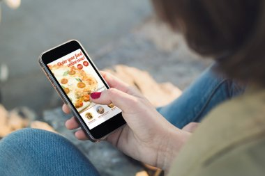 Woman ordering pizza with smartphone
