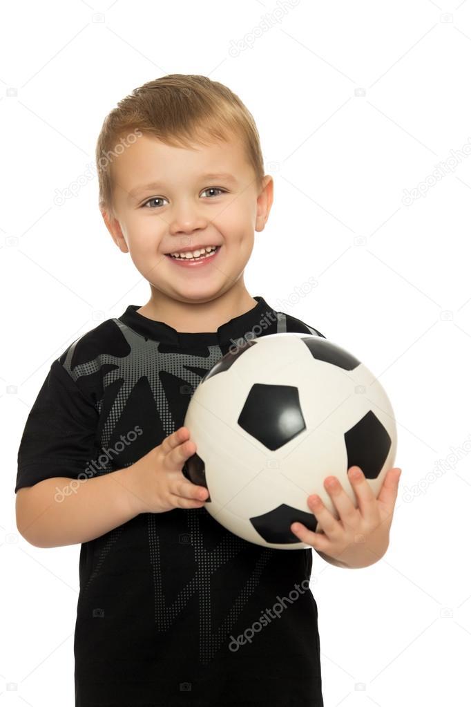 Retrato de un alegre pequeño niño futbolista en uniforme negro. El niño  tiene un balón de fútbol de la mano. Primer plano - aisladas sobre fondo  blanco ... 30bfcf6ebfc9c