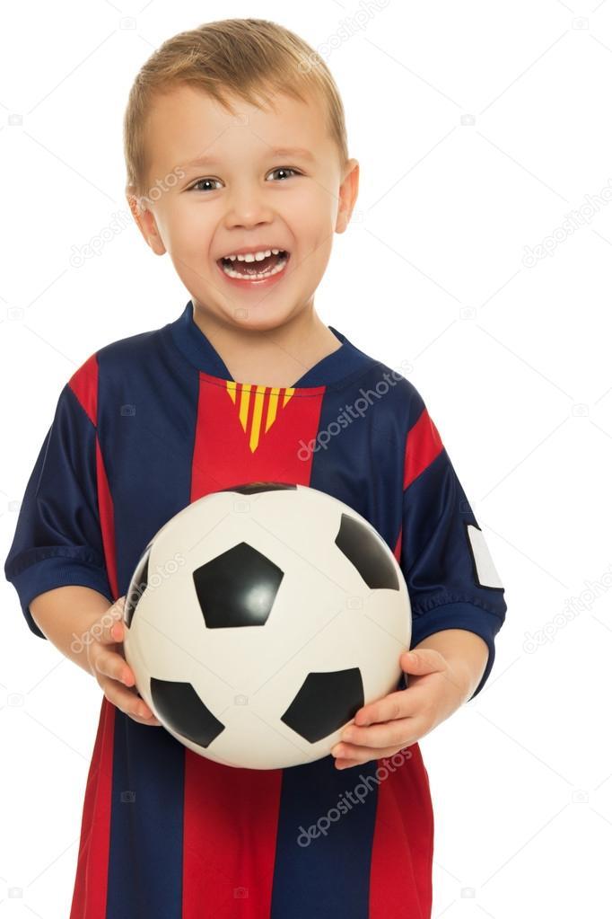 Retrato de un alegre pequeño niño futbolista en un uniforme de rayas. El  niño tiene un balón de fútbol de la mano. Primer plano - aisladas sobre  fondo ... fed63b09d79dd