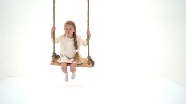 Roztomilé dlouhé vlasy dívka sedí na švihu lana