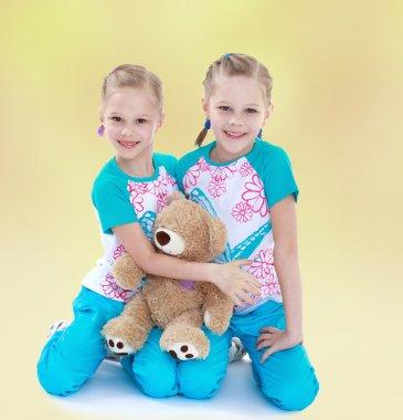 Twin sisters hugging her favorite teddy bear.