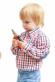 Photo Little boy examines pliers.