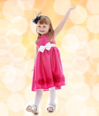 Charming little girl in a pink dress raised her hand up.