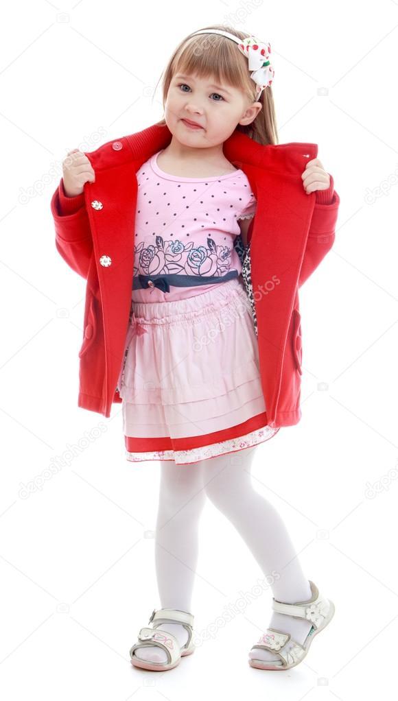 65ccb207186 Πολύ της μόδας κοριτσάκι αποσυμπιέζει ένα όμορφο κόκκινο παλτό. Ευτυχισμένη  παιδική ηλικία, η μόδα, η φθινοπωρινή διάθεση έννοια.
