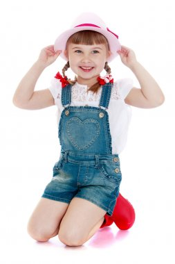 Adorable little girl in denim overalls and a hat