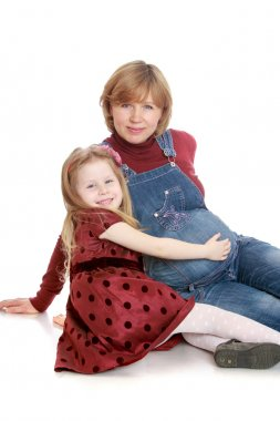 Happy little blonde girl in a long brown dress with polka dots hand stroking the belly of his beloved pregnant mom