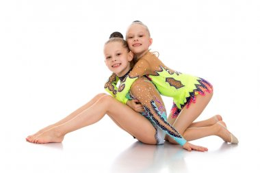 Little gymnasts sitting on the floor