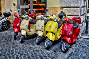 Scooters are parked on the city street in Rome, Italy