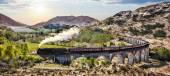 Fotografie Glenfinnan Railway Viaduct in Scotland with the Jacobite steam train against sunset over lake