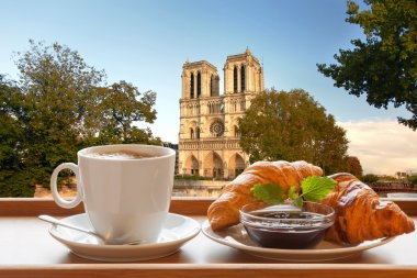 Coffee with croissants against cathedral Notre Dame in Paris, France