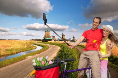 Couple Taking Selfie against  windmills in Zaanse Schans, Amsterdam