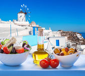 Fotografie Řecký salát proti větrný mlýn ve vesnici Oia, řecký ostrov Santorini