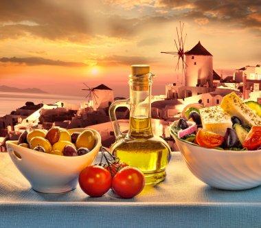 Greek salad against windmill in Oia village, Santorini island in Greece