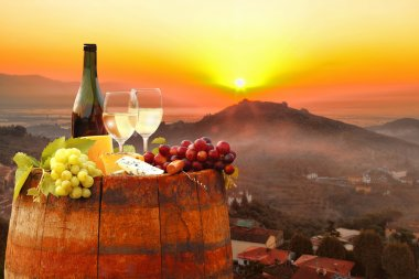White wine with barrel against colorful sunset in Chianti, Tuscany, Italy