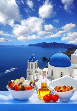 Greek salad against church in Oia village, Santorini island in Greece
