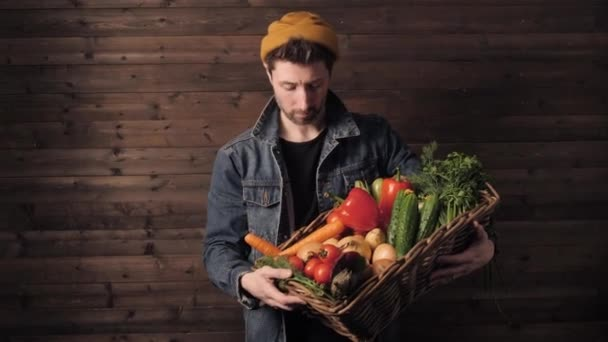 young farmer holds a wicker basket with fresh organic vegetables. small business. Studio shot