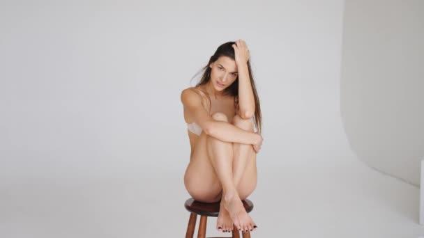 mladá sportovní dívka ve spodním prádle s krásnou postavu pózující ve studiu.