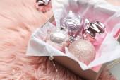 Krásné vánoční ozdoby v krabici na růžové umělé kožešiny