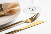 Beautiful table setting with golden cutlery and beige napkin on white background, closeup