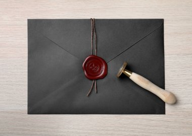 Envelope with wax seal and stamp on white wooden table, top view
