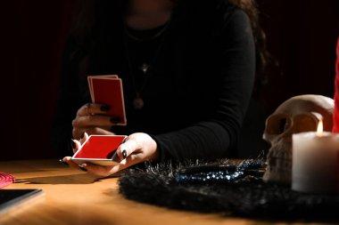 Kahin, kartları kapalı bir masada, yakın planda tutarak geleceği tahmin ediyor.