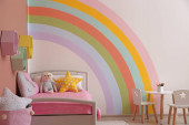 Cute childs room interior with beautiful rainbow painted on wall