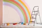 Different decorators tools and ladder near wall with painted rainbow indoors