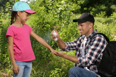 Father spraying tick repellent on his little daughter's arm during hike in nature