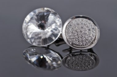 Silver earrings from different sets with rhinestones on the reflecting surface