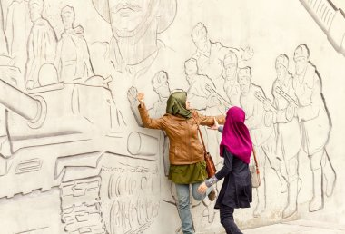Tourists from Asia pose in front of figures describing feats of