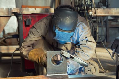 A welder fabricates steel structures using semi-automatic weldin