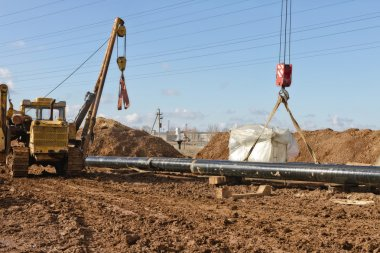 laying of gas main in a trench dug in the field
