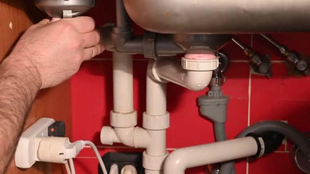 Zkontrolujte odvodňovací okruh pod kuchyňským dřezem. Problémy s instalací, práce související s odvodem. Mužovy ruce kontrolují těsnost trubek. Kontrola je pozitivní: palec nahoru.