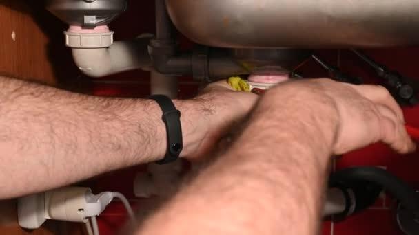 Reparatur des Wasserablaufkreislaufs unter der Küchenspüle. Die Hände des Mannes prüfen die Dichtheit der Rohre, das Wasser fließt, mit Hilfe eines Werkzeugs strafft den Abfluss. Der Check ist positiv: Daumen hoch