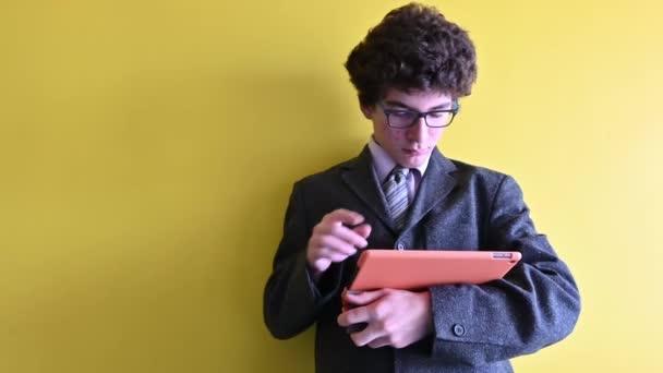 Ein junger kaukasischer Junge berichtet und bereitet sich auf ein Ferninterview mit seinem Tablet mit dem orangefarbenen Umschlag vor. Er scrollt einige Informationen auf den Bildschirm. Konzept des geschäftstüchtigen jungen Journalisten.