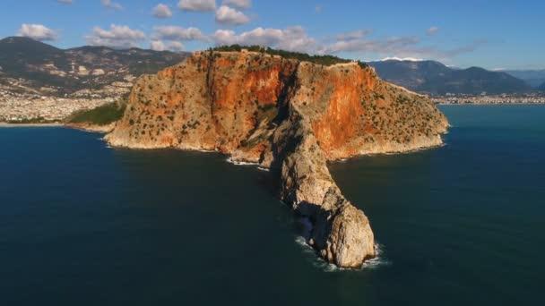 Stadtpanorama von Alanya und Taurusgebirge, überspült vom Mittelmeer. Bewegen Sie den Hubschrauber zurück. Provinz Antalya in der Türkei. Zeitlupe, 4k.