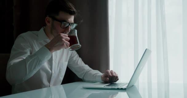 Obchodník v neformálním oblečení pracující na notebooku a pití tee nebo cofee