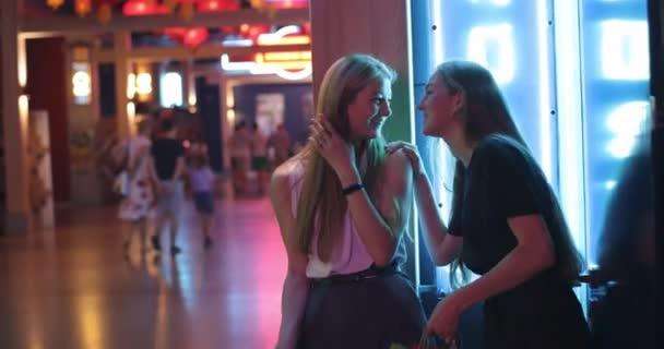 Zwei junge hübsche Damen, die nach erfolgreichem Einkauf spazieren gehen, lächeln und halten Farbpakete in den Händen. Stilvolle Mädchen spazieren durch das Einkaufszentrum und haben Spaß. Ein spannendes Gespräch zwischen