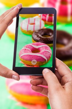 A woman using a smart phone to take a photo of some colorful donuts stock vector