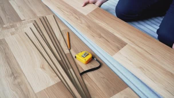 Muž montáž laminované podlahové dlaždice, detail na rukou drží deska, páska opatření, tužka a zásobník dlaždic další