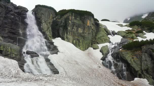 Vodopád Skok na oblačném jarním dni, voda padá do špinavého tání sněhu přes skály