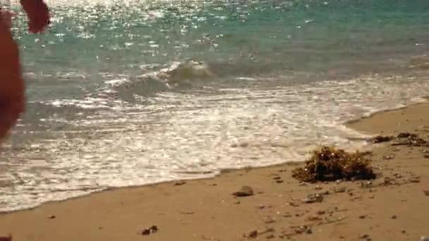 Fiatal nő zöld fürdőruhában sétál a napon kivilágított homok a strandon, részletesen a lábak és a tenger mossa a lábát