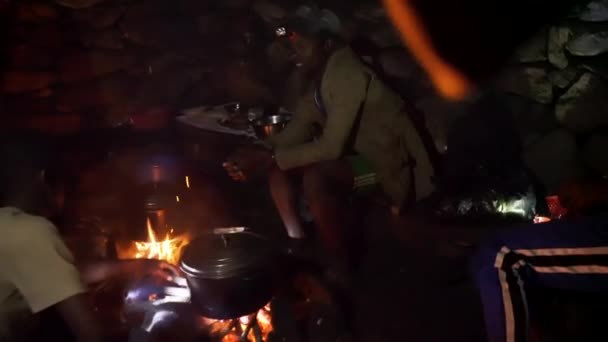 Andringitra National Park, Madagascar - April 27, 2019: Unknown local Malagasy hiking guides preparing dinner on fire at base camp of Pic Boby, night rain with heavy storms outside