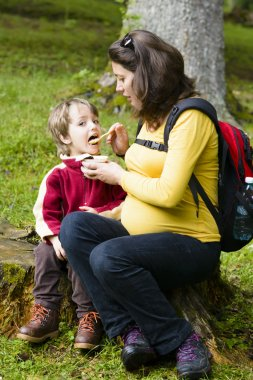 Mother feeding his boy outside in forest