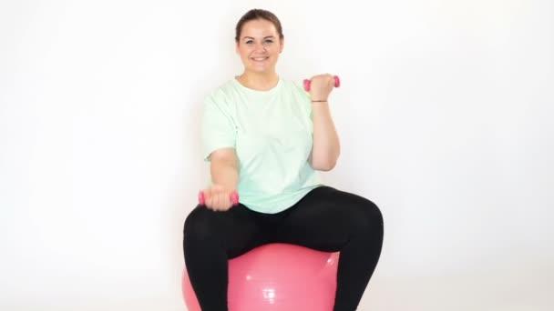 Dicke Frau macht Übungen mit Kurzhanteln auf einem Fitnessball